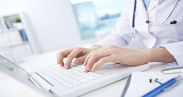 Health care provider typing into keyboard